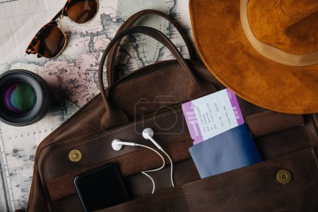 Photo for Top view of leather bag with passport, ticket, smartphone with earphones, sunglasses, lens and hat on map - Royalty Free Image
