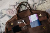 top view of leather bag with passport, ticket, smartphone and earphones on map