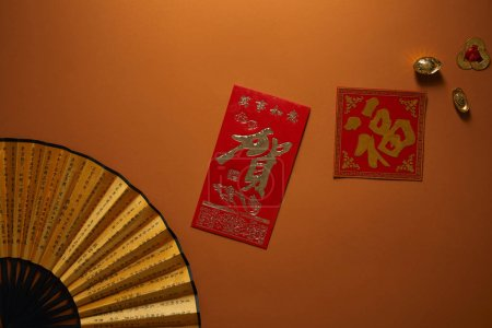 top view of fan with hieroglyphs and golden decorations on brown background, chinese new year composition