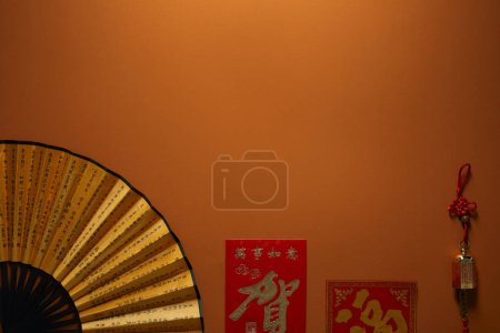 top view of fan with hieroglyphs on brown background, chinese new year composition