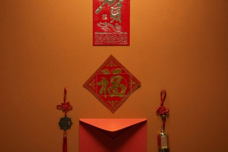 red envelope, hieroglyphs and traditional decorations on brown background, chinese new year concept