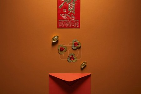 Photo for Top view of red envelope, golden chinese decorations and hieroglyph on brown background - Royalty Free Image