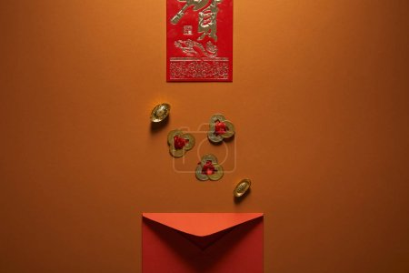 top view of red envelope, golden chinese decorations and hieroglyph on brown background