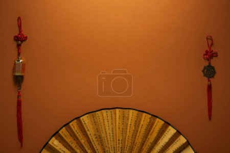 top view of golden fan with hieroglyphs and traditional chinese decorations on brown background
