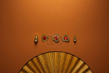 Photo for Top view of traditional golden chinese decorations and fan with hieroglyphs on brown background - Royalty Free Image