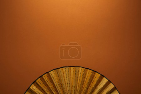 Photo for Top view of traditional golden chinese fan with hieroglyphs on brown background - Royalty Free Image