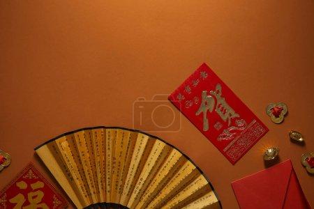 Photo pour Vue de dessus de la composition du nouvel an chinois avec des décorations dorées et ventilateur avec hiéroglyphes sur fond brun - image libre de droit