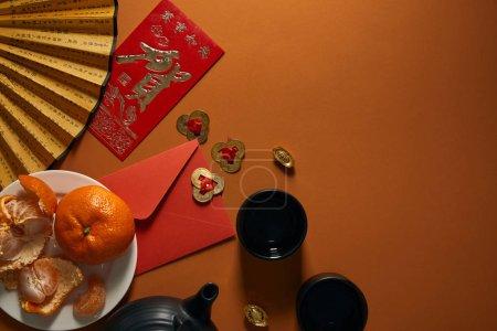 Photo pour Vue de dessus de mandarines sur assiette, ensemble thé noir, ventilateur avec hiéroglyphes, décorations dorées et enveloppe rouge sur fond brun - image libre de droit