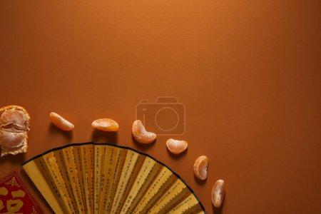 Photo pour Vue de dessus du ventilateur doré avec des hiéroglyphes et mandarine Pelée sur fond marron - image libre de droit