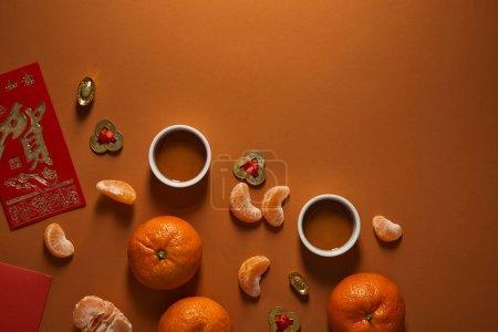 Photo pour Vue du dessus des tasses à thé, des mandarines et des décorations chinoises traditionnelles sur fond brun - image libre de droit