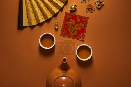 top view of tea set, fan with hieroglyphs and traditional chinese decorations on brown