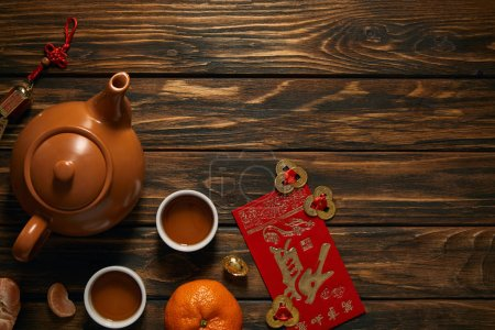 top view of tea set and traditional decorations on wooden table, chinese new year composition