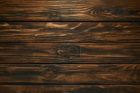 top view of dark brown wooden background with horizontal planks