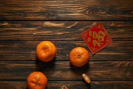 Photo for Top view of fresh ripe tangerines and golden hieroglyph on red on wooden table - Royalty Free Image