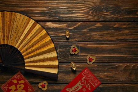 Photo pour Vue de dessus du ventilateur avec hiéroglyphes et décorations chinoises dorées sur table en bois - image libre de droit