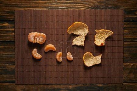 Photo pour Vue de dessus de mandarine Pelée sur la natte de bambou sur la table en bois - image libre de droit