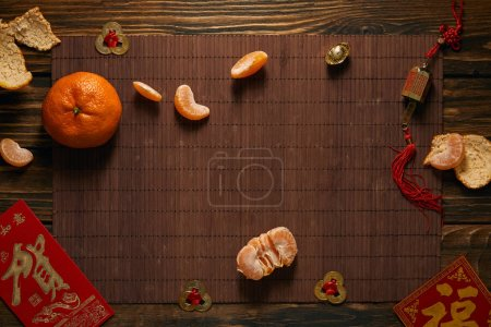Photo for Top view of tangerines and traditional chinese decorations on bamboo mat, chinese new year concept - Royalty Free Image