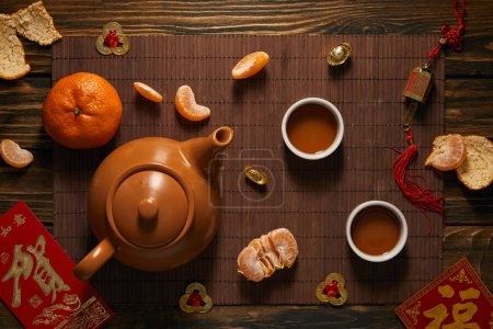 Photo for Top view of tea set, tangerines and traditional chinese decorations on bamboo mat - Royalty Free Image