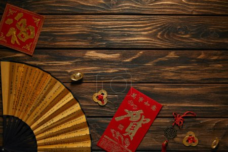 top view of chinese new year composition with fan, hieroglyphs and decorative golden coins on wooden surface
