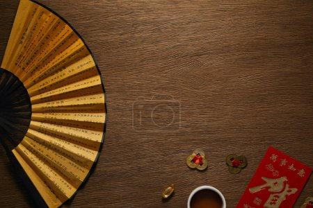 top view of fan with hieroglyphs, golden coins and cup of tea on wooden table
