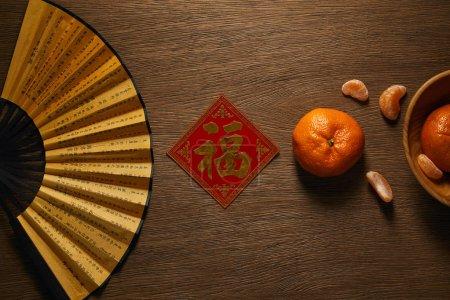 Photo pour Vue de dessus du ventilateur, mandarines fraîches mûres et hiéroglyphe doré décoratif sur table en bois - image libre de droit