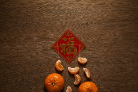 Photo for Top view of fresh ripe tangerines and golden hieroglyph on wooden table - Royalty Free Image