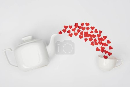 top view of tea pot, cup and heap of red paper cut hearts on white background