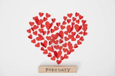 Photo pour Vue du haut des coeurs décoratifs coupés en papier et bloc de bois avec lettrage Février - image libre de droit
