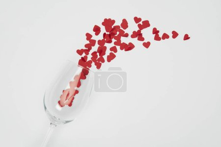 top view of wine glass and small paper cut hearts on white background