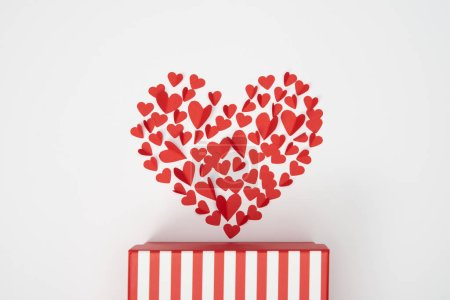 top view of heart shaped arrangement of small red paper cut hearts and striped gift box on white background
