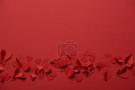 pile of decorative paper cut hearts on red background with copy space