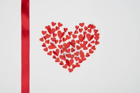 heart shaped arrangement of small red paper cut hearts with satin ribbon on white background