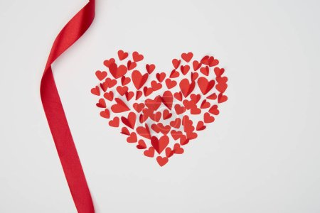 heart shaped arrangement of small paper cut hearts with wavy red ribbon on white background