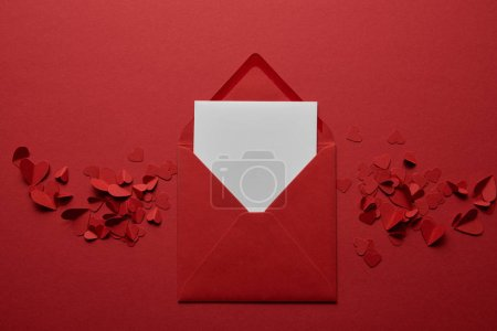 top view of blank white letter in envelope with paper cut hearts on red background