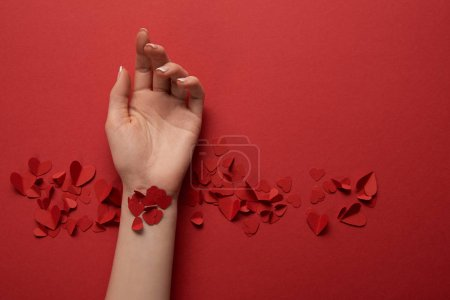 cropped view of female hand with paper cut decorative hearts on red background