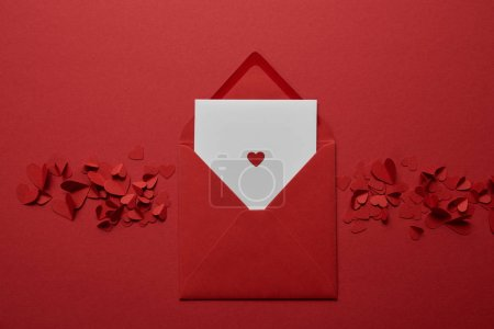 Photo for Top view of white letter in envelope with paper cut hearts on red background - Royalty Free Image