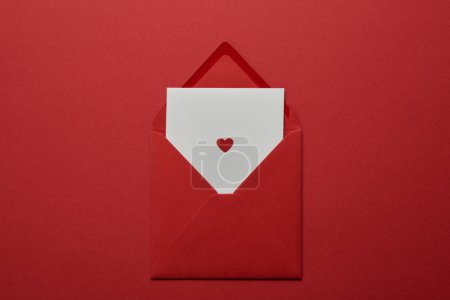 Photo for Top view of white letter with heart in envelope on red background - Royalty Free Image