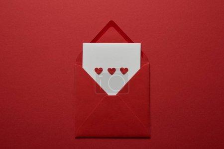 Photo pour Vue de dessus des lettres blanches avec un cœur en enveloppe sur fond rouge - image libre de droit