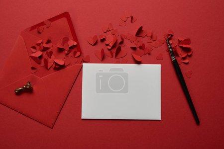 Photo pour Vue du dessus de la lettre blanche vide avec enveloppe, coeurs coupés en papier et stylo sur fond rouge - image libre de droit