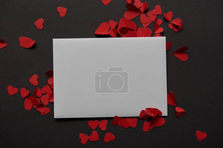 top view of white empty greeting card and red paper cut hearts on black background