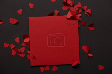 top view of red blank greeting card and paper cut hearts on black background
