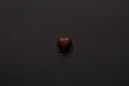 Photo for Top view of tasty chocolate heart on black background - Royalty Free Image