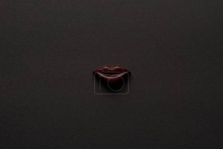 Photo for Top view of tasty chocolate lips on black background - Royalty Free Image