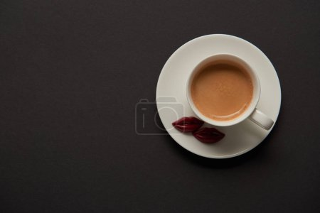 Photo for Top view of cup with coffee and chocolate lips on saucer on black background - Royalty Free Image