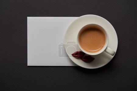Photo pour Vue de dessus de la tasse de café, de chocolat lèvres sur la soucoupe et vide carte blanche sur fond noir - image libre de droit