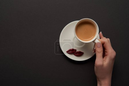 Photo for Top view of woman holding cup of coffee near chocolate lips on saucer - Royalty Free Image