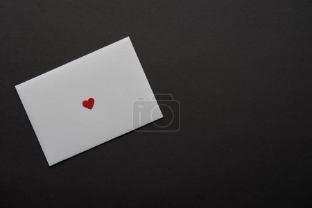 Photo for Top view of white greeting card with red heart sign isolated on black - Royalty Free Image
