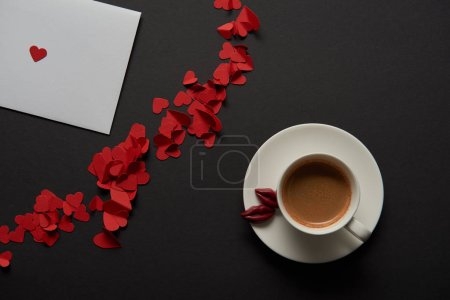 top view of white greeting card with red paper cut hearts and cup of coffee