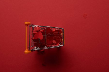 top view of shopping cart with decorative paper cut hearts on red background