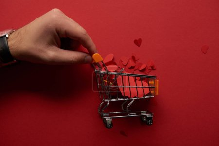 cropped view of male hand and toy shopping cart with paper cut hearts on red background